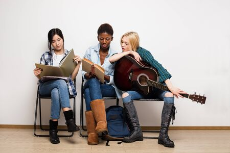 concept of diversity with group of asian, caucasian and afro amirican women having different hobby, white sitting on chairs in a waiting room