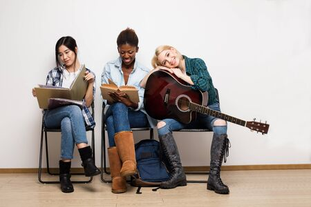 socialization: concept of diversity with group of asian, caucasian and afro amirican women having different hobby, white sitting on chairs in a waiting room