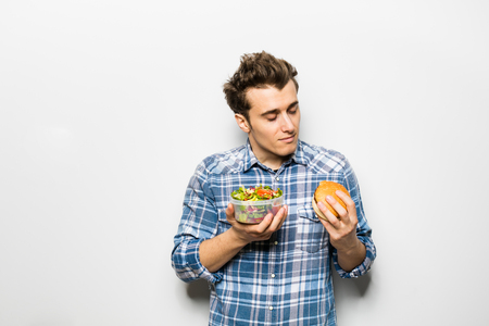 fast food versus healthy food concept with young man holding a salad in one hand and hamburger in the other one, isolated on white Stock Photo