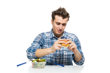 fast food versus healthy food concept with young man eating a hamburger and leaving salad apart