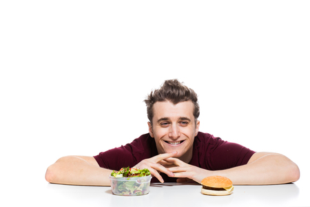 fast food versus healthy food concept with young man having in front two choices, salad and fast food, isolated on white