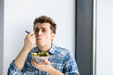 young man eating his vegan salad from a plastic box, his take away lunch at work Stock Photo