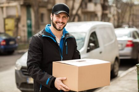 deliverer: Delivery man with cap and cardboard in hands