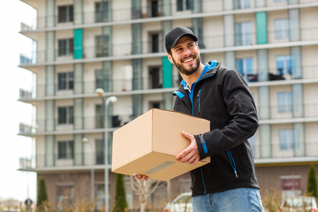 deliverer: Delivery man with cap and cardboard in hands, with blocks behind