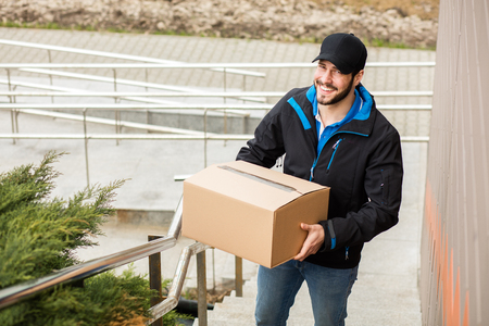 Delivery man with cap and cardboard in hands, climbing a few stairs