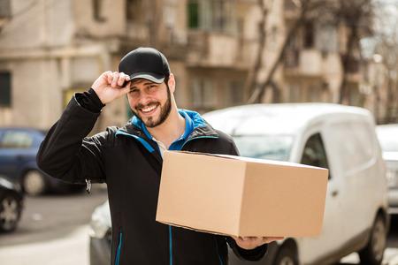 Leveringsmens met GLB en karton in handen die hello aan camera, met zijn bestelwagen op achtergrond zeggen