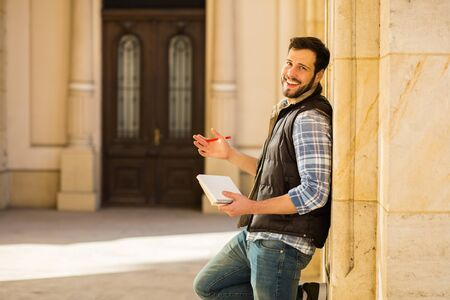 student leaning on university columns with notebook and pen in hands