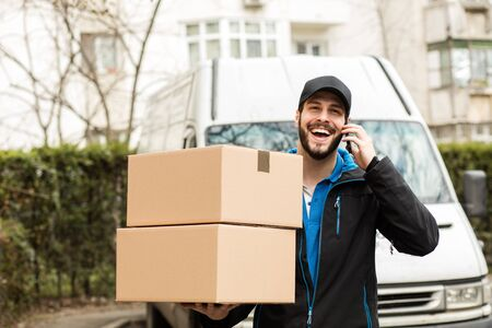 Delivery man with cap and cardboard in hands, talking at cellphone having his van behind Stock Photo