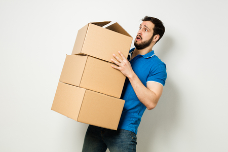 delivery room: bearded young man in blue shirt carrying three carton boxes on a white wall
