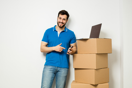 concept of relocation with an adult man standing next to a stack of carton boxes while using an aplication on  cellphone and laptop, on white wall Banco de Imagens