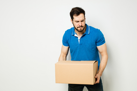 delivery room: man carrying a heavy carton box on a white wall