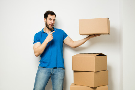 adult man holding a cardboard box over a stack of boxes and presenting it