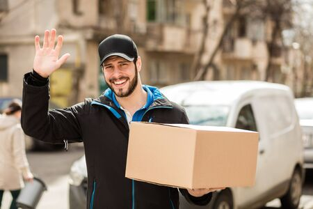 Delivery man with cap and cardboard in hands saying hello to camera, with his van in background