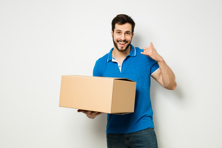 smiling man saying hello to camera with a cardboard box in hands on a white wall