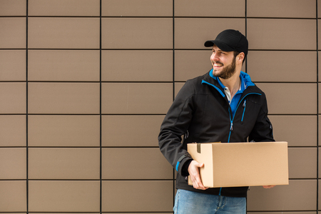 Delivery man with cap and cardboard in hands, somewhere outside on a brown empty background with lines Stock Photo