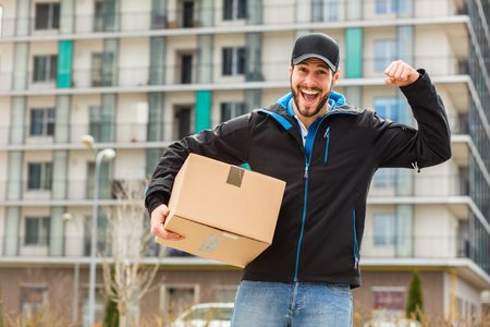 Delivery man with cap and cardboard in hands, with blocks behind