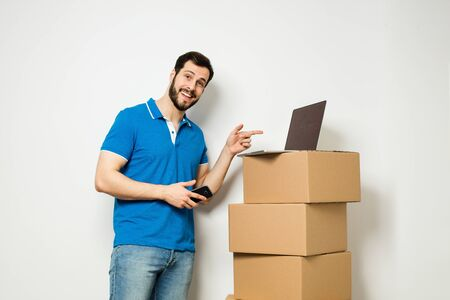 delivery room: concept of relocation with an adult man standing next to a stack of carton boxes while using an aplication on  cellphone and laptop, on white wall Stock Photo