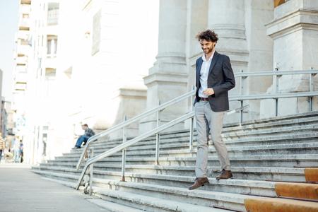エレガントでモダンな男の肯定的な態度で重要な建物の階段を降りて