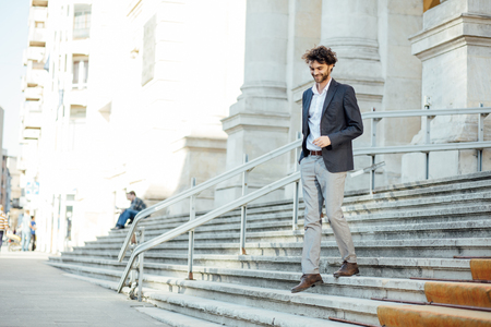 elegant and modern man walking down stairs of important building with positive attitude