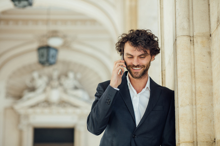 elegant handsome man standing next to columns of an old big building smiling and talking at mobile phone