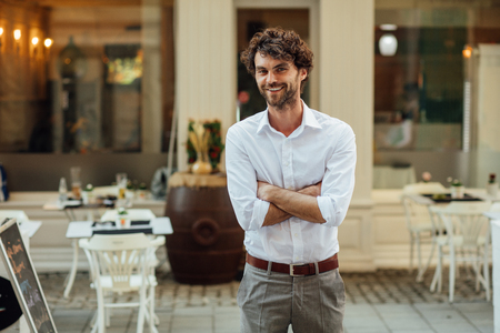 cheerful elegant man, standing outside in the street in front of his restaurant Stock Photo