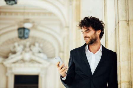 elegant handsome man standing next to columns of an old big building using or talking at mobile phone