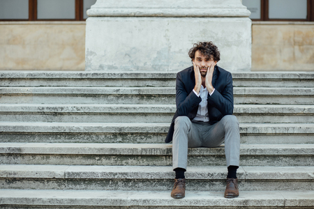handsome man sitting outside concerned on the stairs waiting for someone or something Banque d'images