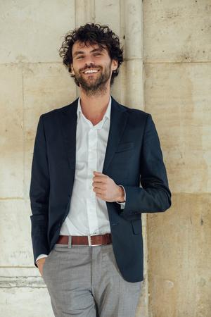 elegant handsome man standing next to columns of an old big building