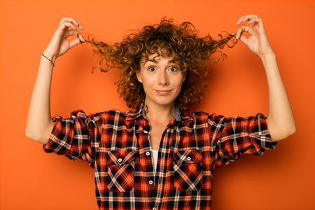 pretty curly woman in a checkered shirt and jeans standing over an orange background with empty space for text next to her