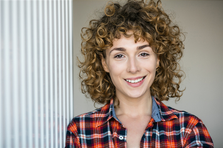 young natural curly woman smiling to camera casual dressed in a checkered shirt inside a house
