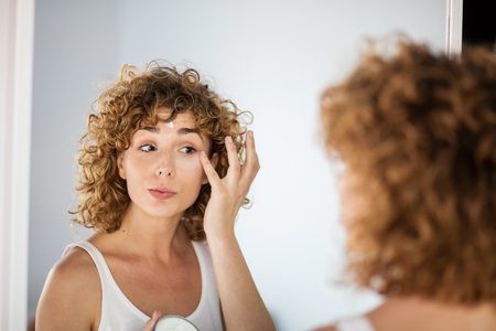 young curly woman using skin cream on in a mirror