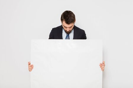 young elegant businessman with white empty panel on white Stock Photo