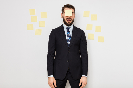 elegant man in suit with postit on his face