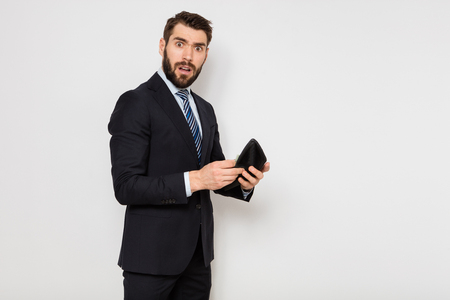 elegant man in suit standing and checking his empty wallet, on white background