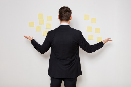 elegant man in suit with postit on the wall Stock Photo