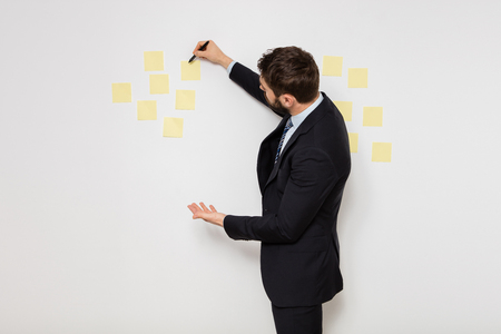 elegant man in suit presenting some postit on the wall Stock Photo