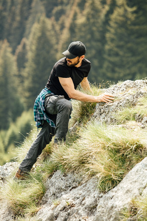 masculine man with beard climbing a rocks in the mountains