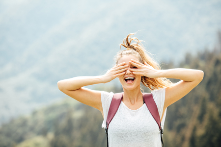 happy young woman with backpack in the mountains very happy covering her eyes Stock Photo