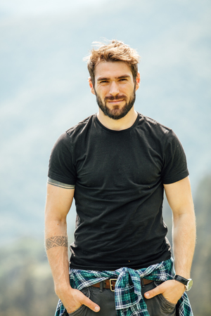 portrait of a young man with beard, somewhere in the middle of the nature Stock Photo