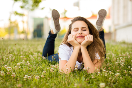 young and beautiful woman lying in green grass, very happy, enjoying the day Foto de archivo
