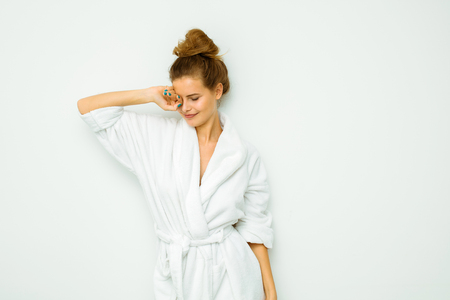 young beautiful woman standing on a white wall in bath towel sleepy