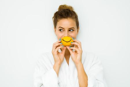 jonge mooie vrouw op een witte muur in badhanddoek spelen met haar favoriete fruit, de citroen