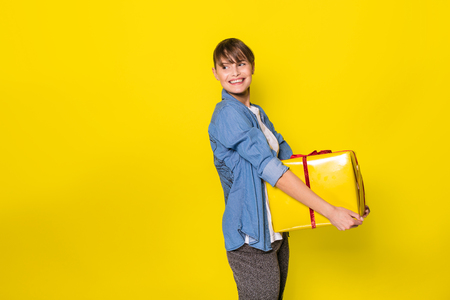 beautiful young woman casual dressed with blue jeans shirt holding a yellow gift box with red ribbon