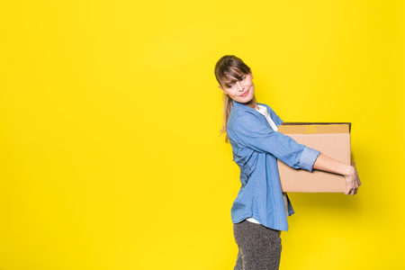 pretty woman standing on yellow background with moving cardboard box Foto de archivo