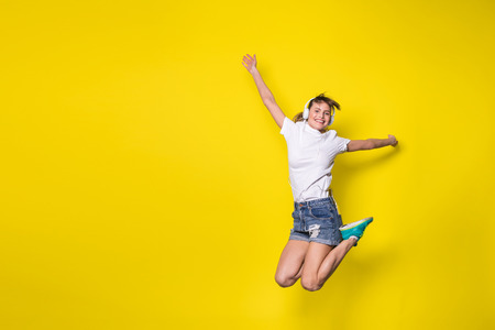 young and happy woman listening music and jumping with big smile on yellow background