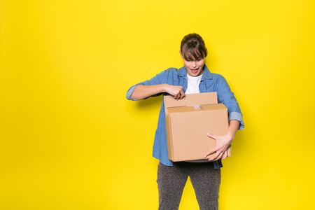 GLÜCKLICHE Frau, die eine Pappschachtel nach neuem Material, auf gelbem Hintergrund untersucht