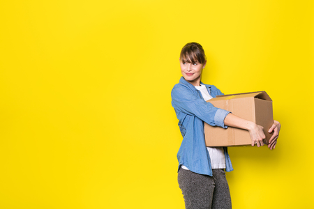 pretty woman standing on yellow background with moving cardboard box 스톡 콘텐츠