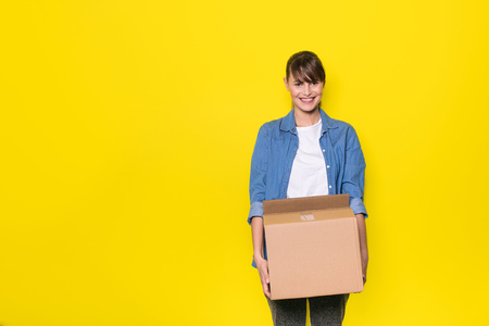 pretty woman standing on yellow background with moving cardboard box 写真素材