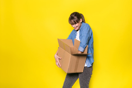 HAPPY woman looking into a cardboard box for new stuff, on yellow background Banque d'images