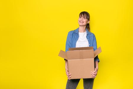 골 판지 상자를 이동하는 노란색 배경에 서있는 예쁜 여자 스톡 콘텐츠